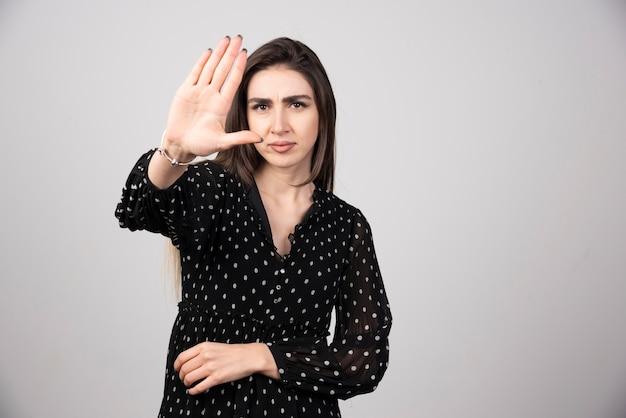 Nette frau im schwarzen kleid, das ihre hand zeigt.