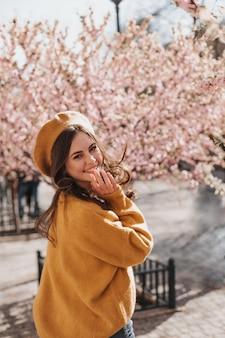 Nette frau im stilvollen orange outfit und lachen auf hintergrund der sakura. attraktive dame im kaschmirpullover und in der baskenmütze, die lächelnd und im park gehen
