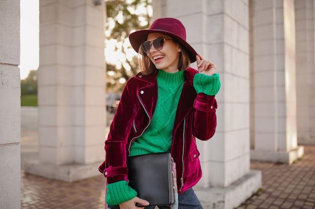 Nette frau im trendigen outfit im herbststil, die auf der straße spaziert