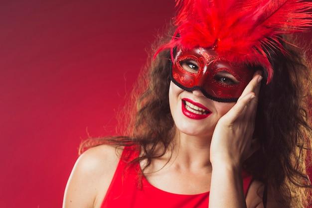 Nette frau in der roten maske mit federn