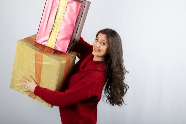 Nette frau in der roten strickjacke, die weihnachtsgeschenke hält.