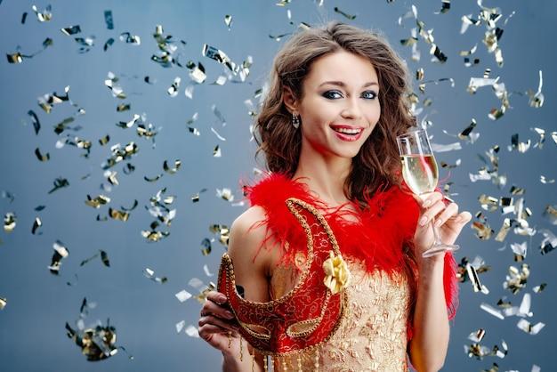 Nette frau in einem goldenen kleid hält in ihrer hand eine rote karnevalsmaske und ein angehobenes glas champagner