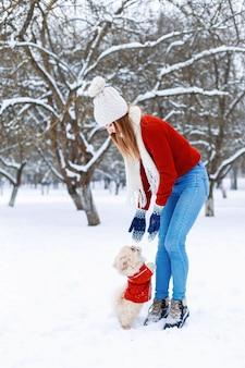 Nette frau in einem weißen strickpullover, der einen pekinesischen welpen an einem wintertag geht