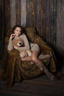 Nette frau in kniestrümpfen und pullover mit teddybär in ihren händen, die im sessel im hölzernen raum sitzen.