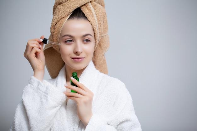 Nette frau macht make-up zum gesicht im badezimmer