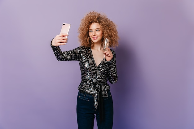 Nette frau mit blonden locken gekleidet in schwarzem paillettenoberteil, das glas champagner hält und selfie auf lila raum macht.