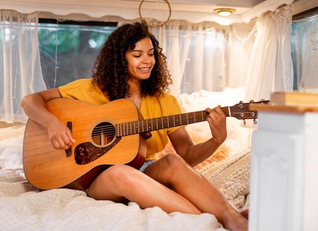 Nette frau mit dem lockigen haar, das akustische gitarre spielt