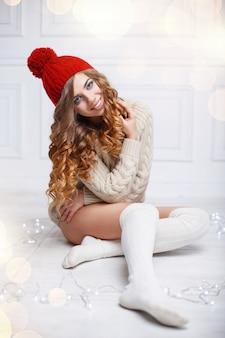 Nette frau mit dem lockigen haar in einem roten weinlesehut, gestrickten pullovern und socken, die auf weißem holzboden sitzen