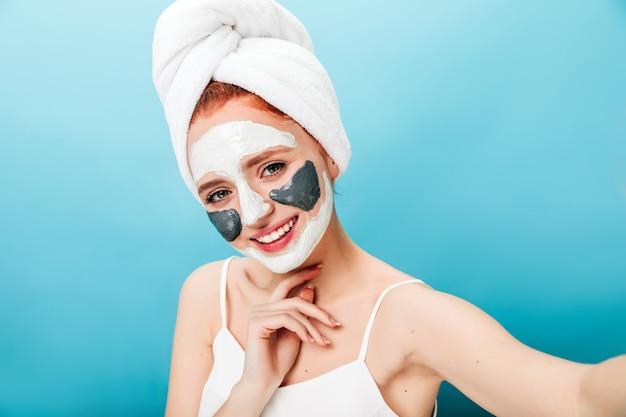 Nette frau mit gesichtsmaske, die selfie mit aufrichtigem lächeln nimmt. studioaufnahme des kaukasischen mädchens, das während der hautpflege-routine aufwirft.