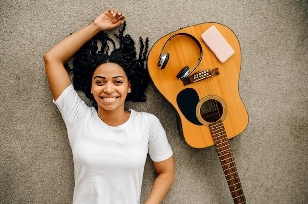 Nette frau mit gitarre und kopfhörern liegend auf dem boden zu hause, draufsicht. hübsche dame mit musikinstrument entspannen im raum, musikliebhaberin ruht sich aus