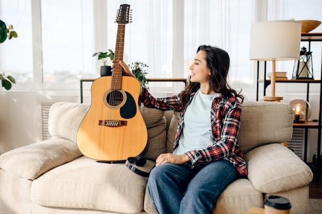 Nette frau mit gitarre zu hause, kopfhörer. hübsche dame mit musikinstrument entspannen sich im zimmer, weibliche musikliebhaberin ruht sich aus?