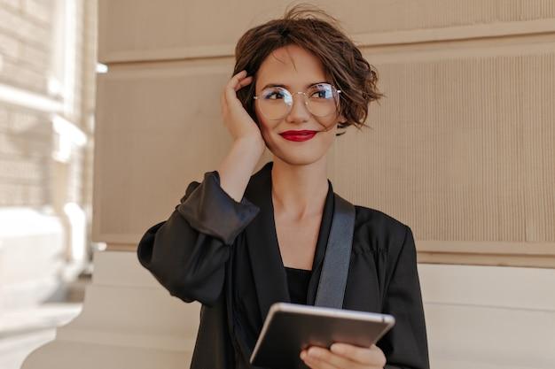 Nette frau mit kurzen haaren und roten lippen, die draußen lächeln. fröhliche frau mit rotem lippenstift in schwarzer kleidung und brille hält tablette im freien.