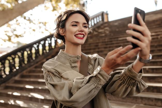 Nette frau mit kurzer frisur und roten lippen, die aufrichtig draußen lächeln. coole frau in jeansjacke macht selfie