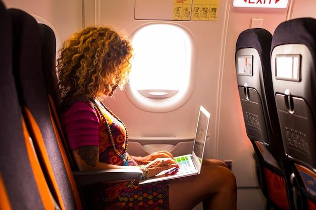Nette frau mit lockigem haar, die im flugzeug sitzt und bereit ist, für das nächste ziel zu fliegen. verwenden sie während der reise einen laptop