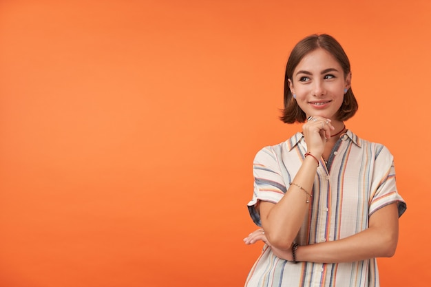 Nette frau mit neugierigem lächeln, das gestreiftes hemd, ringe und armbänder trägt, die hände falten und ihr kinn berühren.