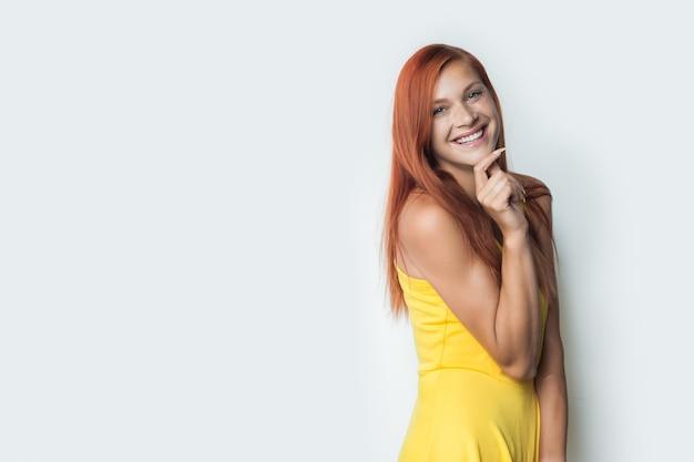Nette frau mit re-dhair und gelbem kleid posiert auf einer weißen wand, die ihr kinn berührt