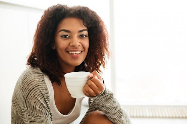 Nette frau mit tasse tee, die auf boden sitzt