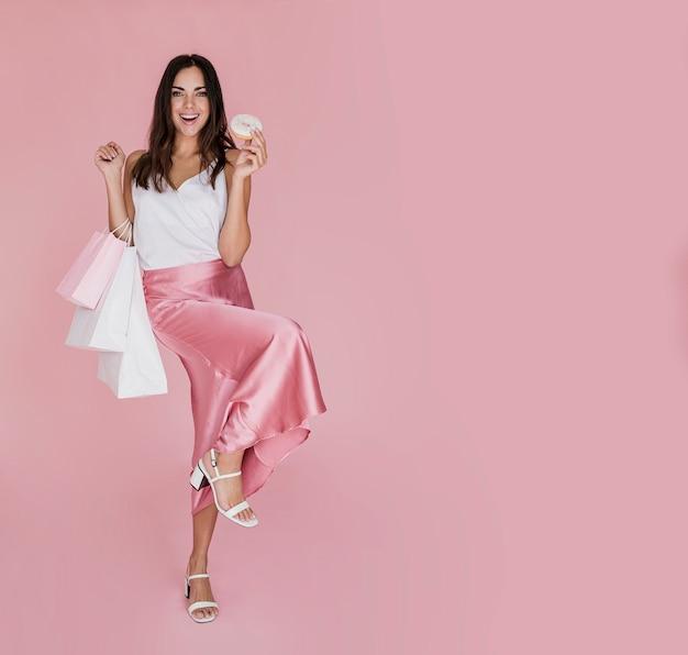 Nette frau mit weißen sandalen auf rosa hintergrund