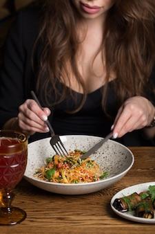 Nette frau sitzt an einem tisch in einem restaurant und beginnt funchoza-salat zu essen.