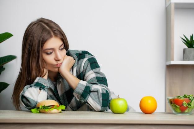 Nette frau trifft eine wahl zwischen gesundem und schädlichem essen