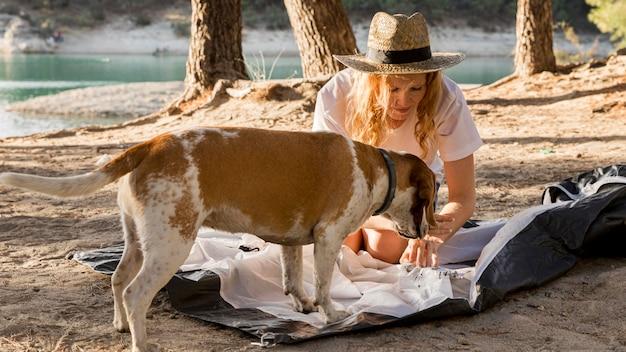 Nette frau und ihr hund stellen das zelt auf