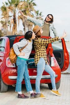 Nette frauen, die selfie auf smartphone nahe dem autokofferraum und dem mann sich lehnen, die sich vom automobil lehnen