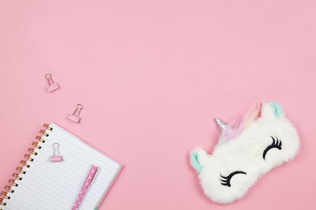 Nette frauen- oder mädchensachen, schlafmasken-einhorn, notizblock, stift, klammern auf rosa hintergrund