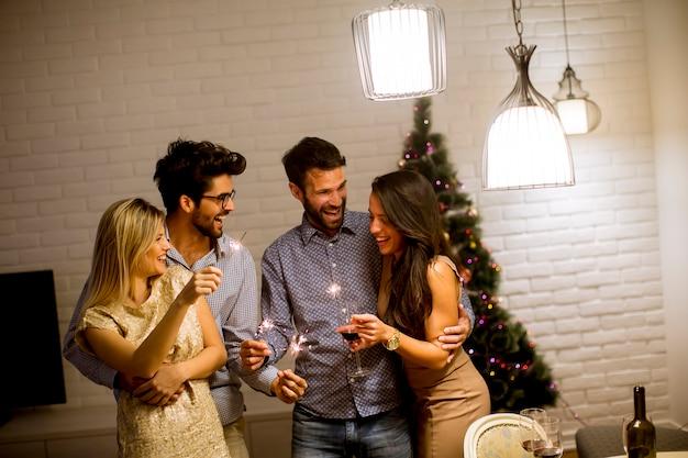 Nette frauen und männer, die zu hause silvester mit scheinen und wein feiern