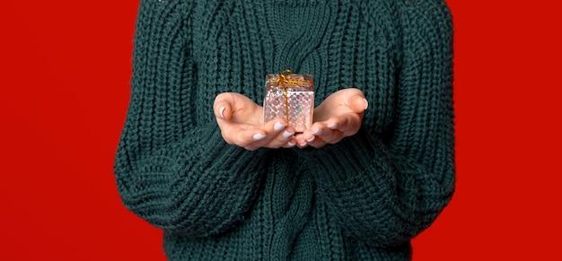 Nette frauenhände halten ein kleines verpacktes geschenk über rotem hintergrund.