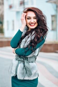 Nette frauenmode des winters. lächelnde frau, die pulloverfellweste trägt. stilvoll gekleidete schöne junge frau in einer pelzweste geht auf der straße