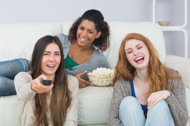 Nette freunde mit fernbedienung und popcornschüssel zu hause
