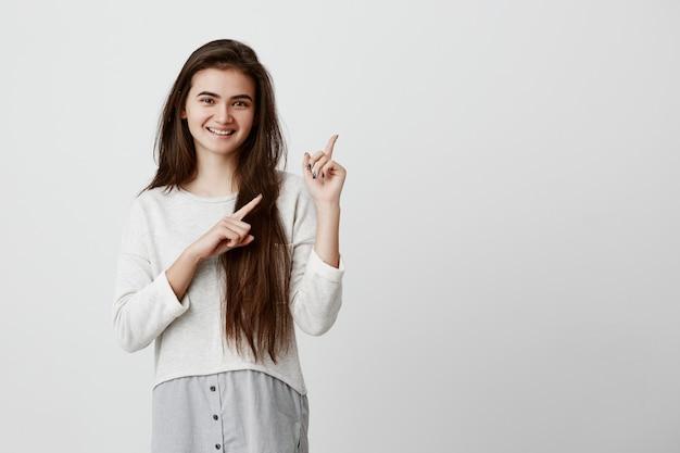 Nette fröhliche brünette junge frau, die finger weg zeigt und etwas interessantes und aufregendes zeigt