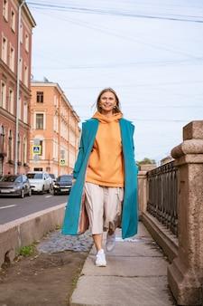 Nette fröhliche frau in einem blauen mantel und einem orangefarbenen pullover mit einer tasche in der hand geht an einem frühlingstag durch die stadt