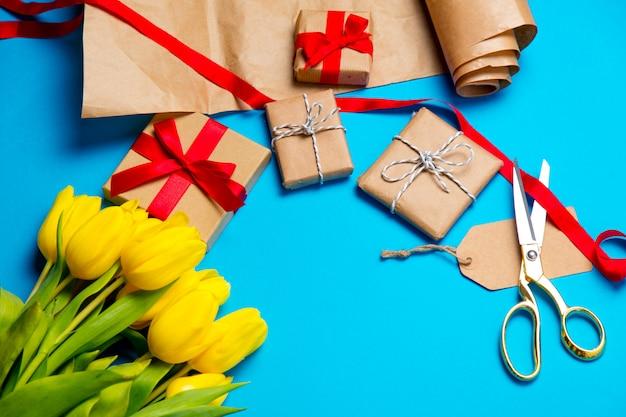 Nette gelbe tulpen, schöne geschenke und kühle dinge für das einwickeln auf dem wunderbaren blauen hintergrund