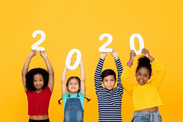 Nette gemischte rassenkinder, die lächeln und 2020 zahlen halten