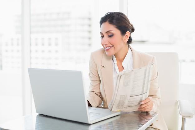 Nette geschäftsfrau, die zeitung beim arbeiten an laptop hält