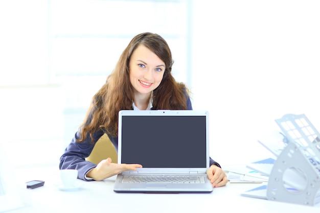 Nette geschäftsfrau im büro, darstellung des laptops.