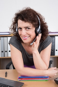 Nette geschäftsfrau im büro lächelnd im call-center
