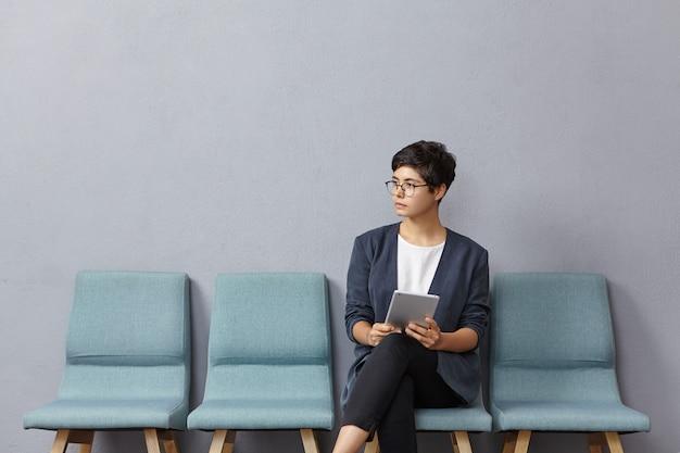 Nette geschäftsfrau schaut nachdenklich zur seite, wartet auf treffen mit partnern