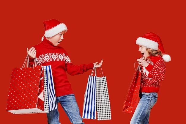 Nette geschwister im roten pullover, der einkaufstaschen hält