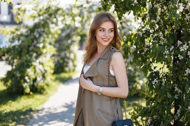 Nette glückliche attraktive junge frau in einer stilvollen sommerweste in einem weißen t-shirt mit einer schwarzen lederhandtasche, die in einem park nahe den grünen blühenden bäumen aufwirft. schönes mädchen lächelnd