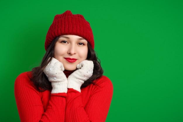 Nette glückliche frau in der roten strickmütze, im pullover und in den handschuhen auf grünem hintergrund.