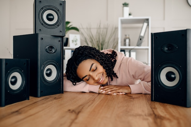 Nette glückliche frau zwischen vielen audio-lautsprechern