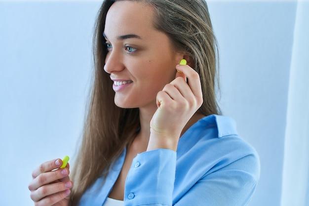Nette glückliche junge brünette frau, die ohrstöpsel benutzt. lärmschutz