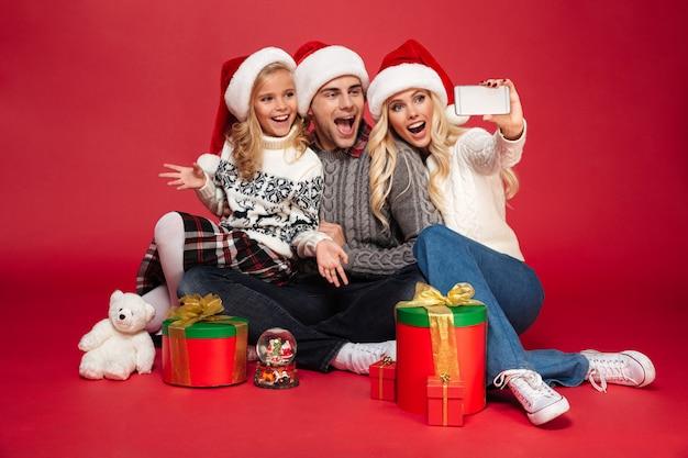 Nette glückliche junge familie, die weihnachtshüte trägt, machen selfie