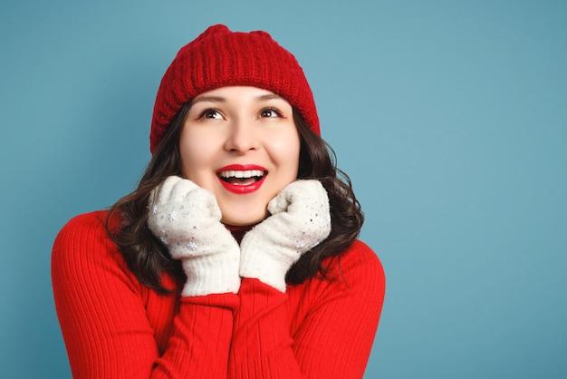 Nette glückliche junge frau in der roten strickmütze, im pullover und in den handschuhen auf blauem hintergrund.