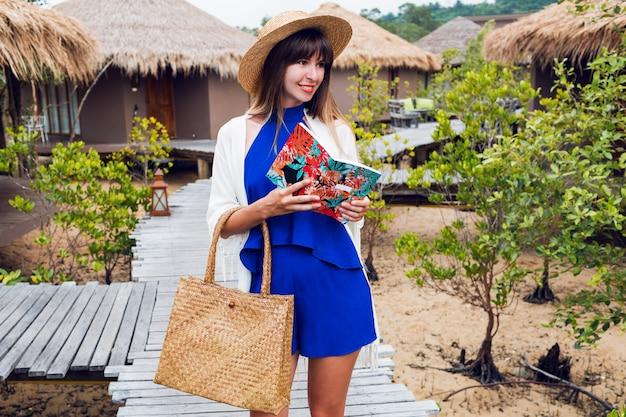 Nette glückliche reisende frau mit dem notizbuch, das a.blauen overall, strohhut und tasche, sonnenbrille lächelt. brünettes mädchen, das in ihrer erstaunlichen luxusvilla aufwirft.