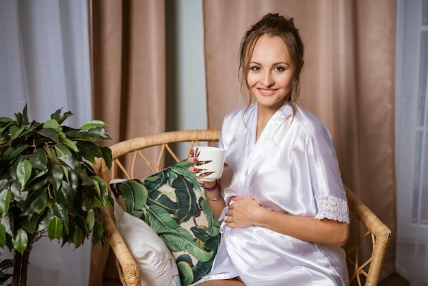 Nette glückliche schwangere frau in einem weißen kittel im neunten monat der schwangerschaft, sitzend in einem stuhl mit einem becher in ihrer hand