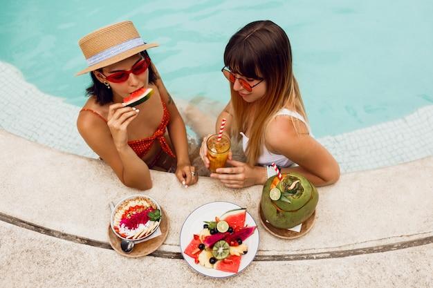 Nette glückselige freunde, die leckeres veganes essen im pool während des tropischen urlaubs in bali genießen. teller mit exotischen früchten. partystimmung.