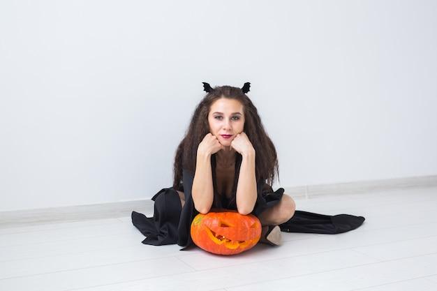 Nette gotische frau in halloween-artkleidung mit kürbis in den händen über heller oberfläche mit kopienraum